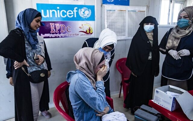 A woman receives a shot of a COVID-19 vaccine in the Kurdish-run al-Hol camp in Hasakeh governorate in northeastern Syria, on June 23, 2021. (Delil Souleiman/AFP)