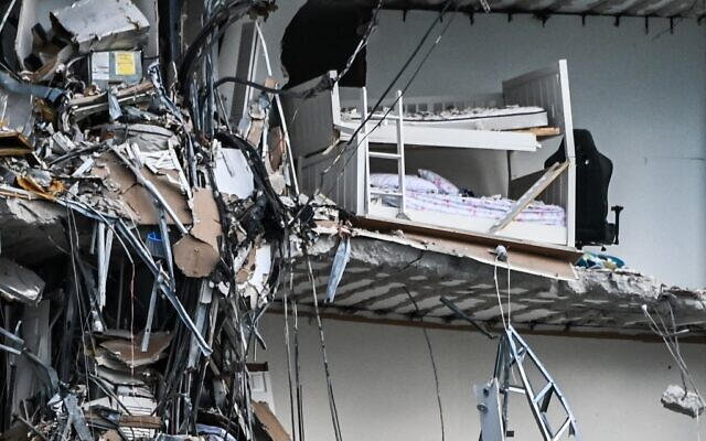 Rubble hangs from a partially collapsed building in Surfside north of Miami Beach, on June 24, 2021. - The multi-story apartment block in Florida partially collapsed early June 24, sparking a major emergency response. (CHANDAN KHANNA / AFP)