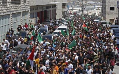 Mourners walk in a funeral procession with the body of Palestinian Authority critic Nizar Banat, who died shortly after being arrested by the PA a day before in Hebron on June 25, 2021 (Photo by MOSAB SHAWER/AFP)