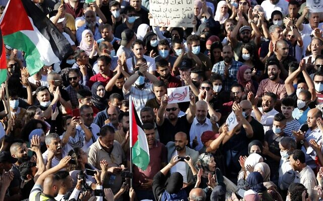 Palestinians lift placards and national flags during a demonstration in the city of Ramallah in the West Bank, on June 26, 2021, to protest the death of human rights activist Nizar Banat while in the custody of Palestinian Authority (PA) security forces. (Ahmad GHARABLI / AFP)