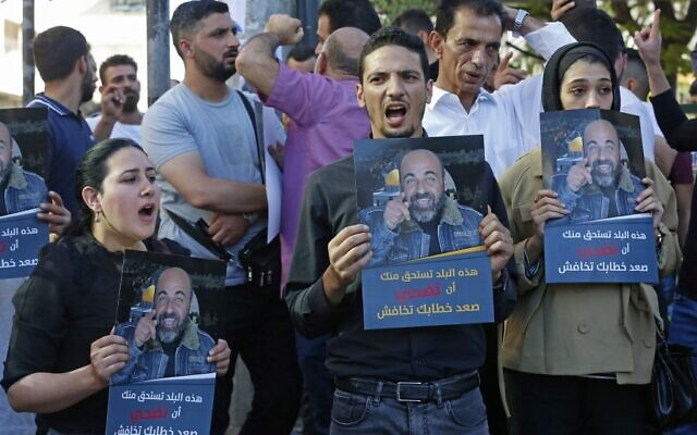 Palestinians hold posters depicting human rights activist Nizar Banat during a protest triggered by the violent arrest and death in custody of Banat, in his hometown of Hebron in the occupied West Bank, on June 27, 2021. (MOSAB SHAWER / AFP)