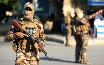 Illustrative: Hashed al-Shaabi paramilitary fighters stand guard during a funerary procession in the Iraqi capital Baghdad, October 26, 2019. (Ahmad Al-Rubaye/AFP)