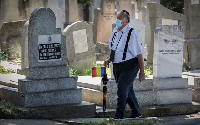 A member of the Jewish community walks at the Jewish cemetery in the city of Iasi, Romania, on June 29, 2021. (Liviu Chirica/AFP)