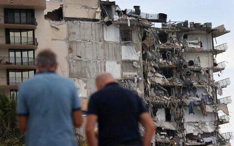 People look at a portion of the 12-story Champlain Towers South condo building that partially collapsed on June 24, 2021 in Surfside, Florida. (JOE RAEDLE / GETTY IMAGES NORTH AMERICA/Getty images via AFP)
