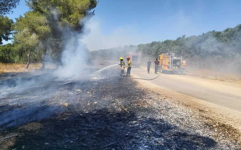 Fire and rescue services put out a fire allegedly sparked in the Western Negev by arson balloons launched by Gaza terrorists, June 16, 2021. (Itzik Lugasi/KKL-JNF)