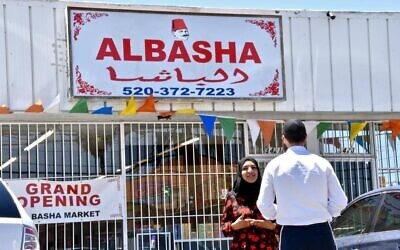 Ghufran Almusawi, proprietor of Al Basha Grocery in Tucson, Arizona, speaks with a Jewish customer. Her store sells both kosher and halal products in an effort to create a 'melting pot' for Jews and Muslims. (Michael Zaccaria/Keeping Jewish/ via JTA)
