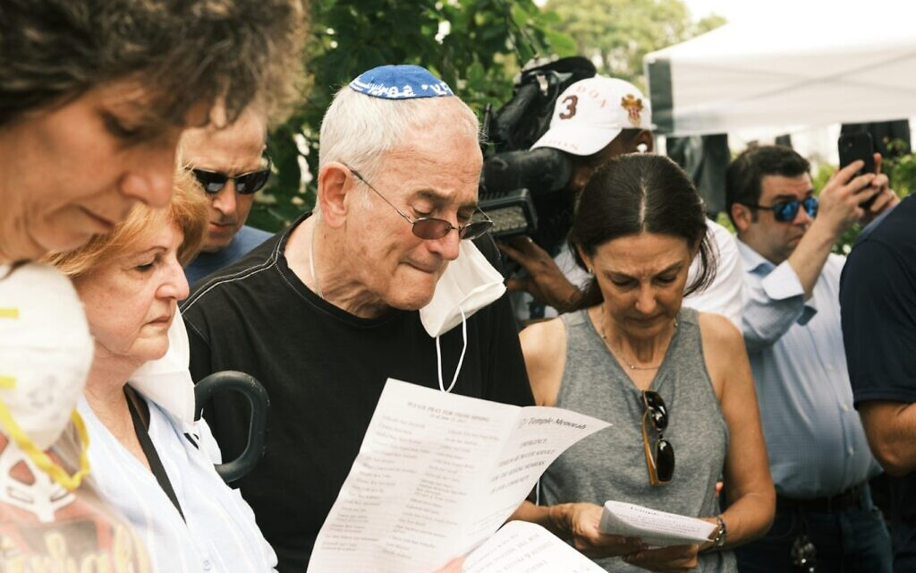 Rabbi Eliot Pearlson, in kippah, leads a psalm reading as he speaks to members of his congregation in the wake of the collapse of the Champlain Towers in Surfside, Fla., June 25, 2021. Pearlson, who has a number of his congregates among those missing, is the rabbi at Temple Menorah just a few blocks from the collapsed condos. (Zack Wittman for The Washington Post via Getty Images via JTA)
