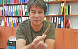 Prehistorian Dr. Omry Barzilai with a flint tool from 50,000-year-old Boker Tachtit. (Israel Antiquities Authority)
