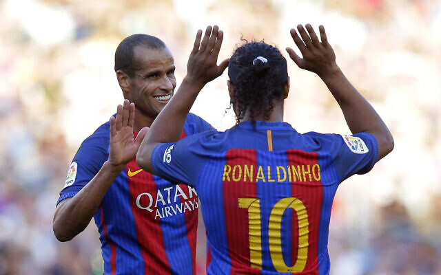 Former FC Barcelona player Ronaldinho, right, gestures to his teammate Rivaldo during a friendly soccer match between FC Barcelona legends and Manchester United legends at the Camp Nou stadium in Barcelona, Spain, June, 30, 2017. (AP Photo/Manu Fernandez)