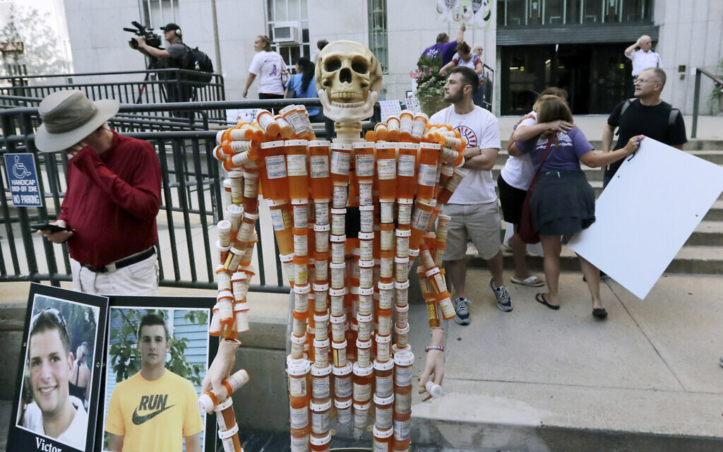 A skeleton made of pill bottles stands with protesters outside a courthouse in Boston, where a judge was to hear arguments in Massachusetts' lawsuit against Purdue Pharma over its role in the national drug epidemic, August 2, 2019. (AP Photo/Charles Krupa)