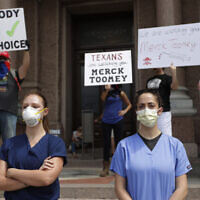 """Health care workers wearing scrubs and face masks watch as protesters hold an """"Open Texas"""" rally at the Texas State Capitol, Saturday, April 25, 2020, in Austin, Texas. (AP Photo/Eric Gay)"""