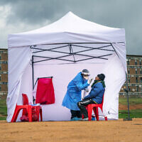 In this Wednesday, April 29, 2020 file photo, a resident from the Alexandra township gets tested for the new coronavirus, in Johannesburg, South Africa. (AP Photo/Jerome Delay, File)