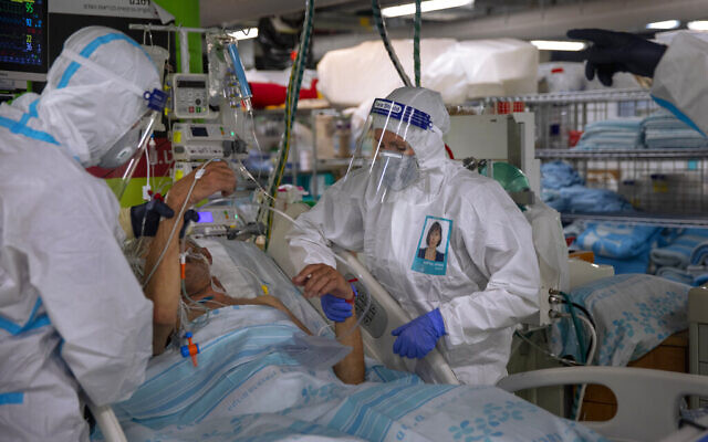 Medical personnel wearing protective equipment treat a COVID-19 patient in an intensive care ward that has been converted from underground parking, at Rambam Hospital in the northern Israeli city of Haifa, December 15, 2020. The underground facility originally built for a war emergency, can turn from a parking garage into a protected hospital within 72 hours and has been treating coronavirus patients since September 2020. (AP Photo/Oded Balilty)