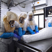 Workers prepare a body before a funeral procession at a special morgue for people who died from COVID-19 in the central Israeli city of Holon, near Tel Aviv, January 10, 2021. (AP Photo/Oded Balilty)