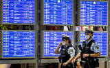 German police officers wearing face mask walk past a flight board in a terminal at the airport in Frankfurt, Germany, Tuesday, May 11, 2021. (AP Photo/Michael Probst)