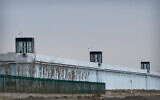 A person stands in a tower on the perimeter of the Number 3 Detention Center in Dabancheng in western China's Xinjiang Uyghur Autonomous Region on April 23, 2021. Human rights groups and Western nations led by the United States, Britain and Germany accused China of massive crimes against the Uyghur minority and demanded unimpeded access for U.N. experts  (AP Photo/Mark Schiefelbein)