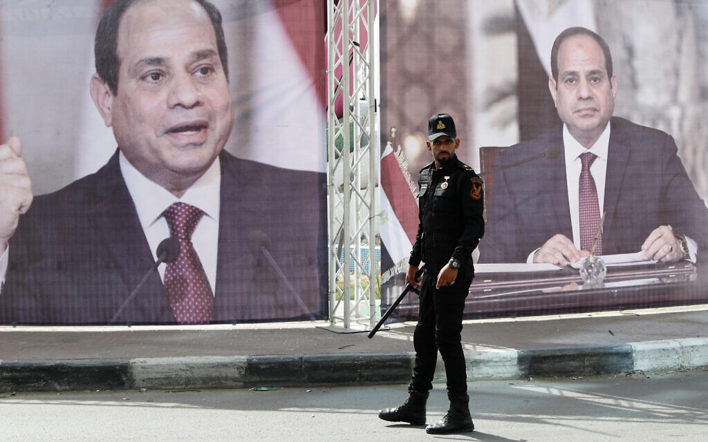 A Hamas police officer stands guards at the main square in front of large portraits of Egyptian President Abdel Fattah el-Sissi, while Hamas leaders meet with Egypt's intelligence chief Abbas Kamel, unseen, in Gaza City, May 31, 2021. (AP Photo/Adel Hana)