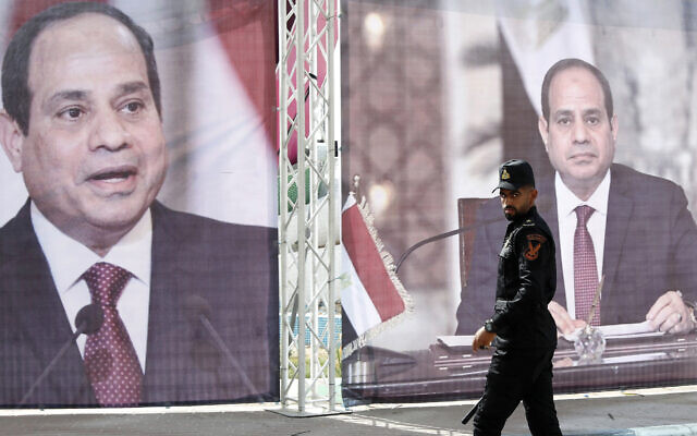 A Hamas police officer walks in front of large portraits of Egyptian President Abdel Fattah el-Sissi, while Hamas leaders meet with Egypt's intelligence chief Abbas Kamel in Gaza City, May 31, 2021. (Adel Hana/AP)