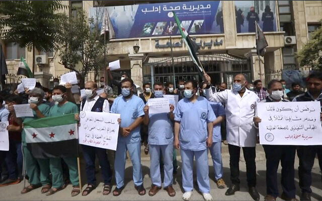 In this image taken from video, dozens of medical workers protest a decision to grant Syrian President Bashar Assad's government a seat on the executive board of the World Health Organization, Monday, May 31, 2021, in Idlib, Syria.  (AP)