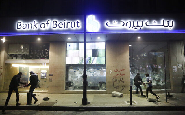 In this January 14, 2020 file photo, anti-government protesters smash a bank widow during protests against the Lebanese central bank's governor and against the deepening financial crisis, at Hamra trade street, in Beirut, Lebanon. (AP Photo/Hussein Malla, File)