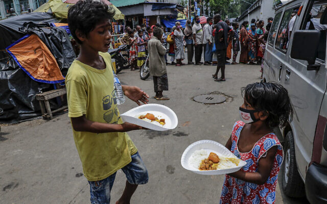 Children living in a slum receive free meal distributed by a voluntary organization during a lock down to curb the spread of coronavirus pandemic in Kolkata, India,  June 2, 2021. (AP Photo/Bikas Das)
