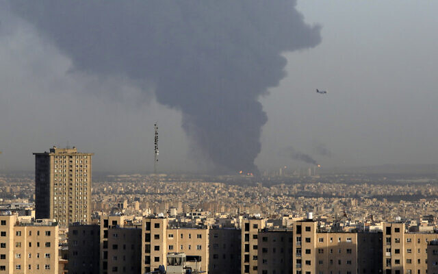 Huge smoke rises from Tehran's main oil refinery as a plane approaches Mehrabad airport south of Tehran, Iran, June 2, 2021. A massive fire broke out Wednesday night at the oil refinery serving Iran's capital, sending thick plumes of black smoke over Tehran. (AP Photo/Vahid Salemi)