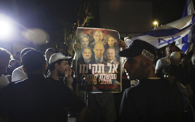 Israeli police officers stand guard as right-wing protesters chant slogans and hold signs showing Naftali Bennett and other members of the Yamina party with Arab politicians Ahmad Tibi, right, and Mansour Abbas, left, during a demonstration in the central Israeli city of Ramat Gan, June 2, 2021. The Hebrew sign reads, 'Don't form a left-wing government with supporters of terror.' (AP/Sebastian Scheiner)