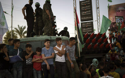 Palestinians gather as Hamas members parade at a rally just over a week after a ceasefire was reached in an 11-day war between the terror group and Israel, May 30, 2021, in Beit Lahia, northern Gaza Strip. (AP Photo/Felipe Dana)