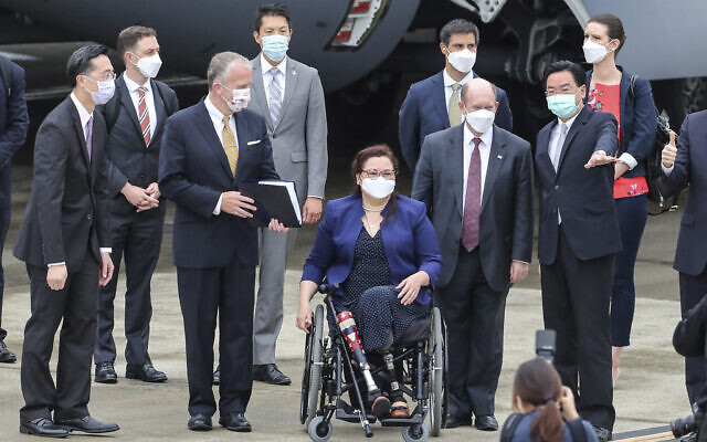 Taiwan's Foreign Minister Joseph Wu, second right, gestures as he welcomes US senators to his right Democratic Sen. Christopher Coons of Delaware, a member of the Foreign Relations Committee, Democratic Sen. Tammy Duckworth of Illinois and Republican Sen. Dan Sullivan of Alaska, members of the Armed Services Committee on their arrival at the Songshan Airport in Taipei, Taiwan on Sunday, June 6, 2021. (Pool Photo via AP)