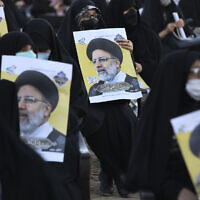 Supporters of the presidential candidate Ebrahim Raisi, currently judiciary chief, hold his posters during a campaign rally in town of Eslamshahr southwest of the capital Tehran, Iran, June 6, 2021. (AP Photo/Vahid Salemi)