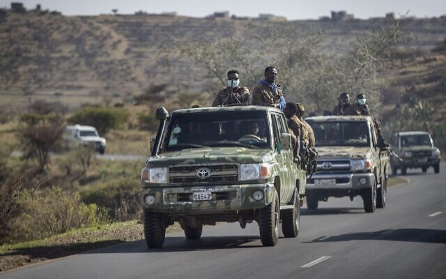 Ethiopian government soldiers ride in the back of trucks on a road near Agula, in the Tigray region of northern Ethiopia, on Saturday, May 8, 2021. (AP Photo/Ben Curtis)