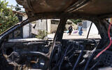 A car belonging to an Arab family sits torched from recent clashes between Arabs, police and Jews in the mixed Arab-Jewish town of Lod, central Israel, May 25, 2021 (AP Photo/David Goldman)