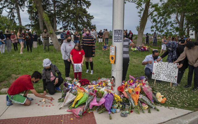 People attend a memorial at the location where a family of five was hit by a driver, in London, Ontario, June 7, 2021 (Brett Gundlock/The Canadian Press via AP)