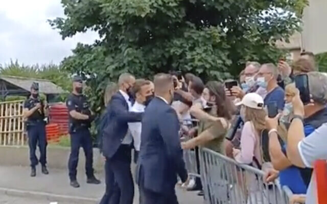 In this grab taken from video France's President Emmanuel Macron, center, is slapped by a man, in green T-shirt, during a visit to Tain-l'Hermitage, in France on June 8, 2021. (BFM TV via AP)