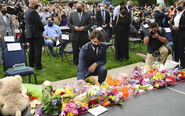 Canada's Prime Minister Justin Trudeau lays flowers at a vigil outside the London Muslim Mosque for the victims of the deadly vehicle attack on five members of the Canadian Muslim community in London, Ontario, June 8, 2021. (Nathan Denette/The Canadian Press via AP)