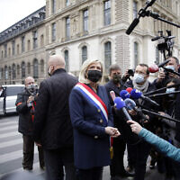 French far-right leader Marine le Pen, center, talks to media after laying a wreath during a ceremony in Paris on May 1, 2021. (AP Photo/Thibault Camus)