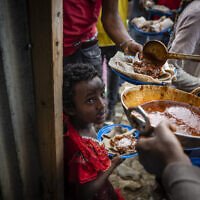 Elena, 7, center, lines up with other displaced Tigrayans to receive food donated by local residents at a reception center for the internally displaced in Mekele, in the Tigray region of northern Ethiopia, on May 9, 2021 (AP Photo/Ben Curtis)