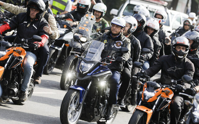 Brazil's President Jair Bolsonaro, center,  takes part in a caravan of motorcycle enthusiasts who gathered in a show of support for Bolsonaro, in Sao Paulo, Brazil, June 12, 2021. (AP Photo/Marcelo Chello)