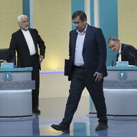 In this picture made available by Young Journalists Club, YJC, presidential candidates for June 18, elections Saeed Jalili, left, Abdolnasser Hemmati, center, and Alireza Zakani, conclude a part of the final debate of the candidates at a state-run TV studio in Tehran, Iran, Saturday, June 12, 2021. (Morteza Fakhri Nezhad/ Young Journalists Club, YJC via AP)
