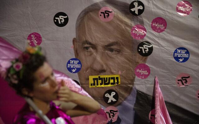 An Israeli protester wears pink during a demonstration against Israeli Prime Minister Benjamin Netanyahu outside his official residence in Jerusalem, June 12, 2021. (AP Photo/Ariel Schalit)