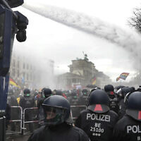 In this file photo, police use water canons to clear a blocked road near the German federal parliament, as people attend a protest rally in Berlin, Germany, against the coronavirus restrictions in Germany in July 2020. (AP Photo/Michael Sohn, file)