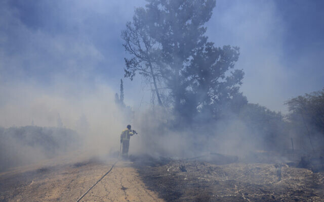 An Israeli firefighter attempts to extinguish a fire caused by an incendiary balloon launched by Palestinians from the Gaza Strip, on the Israel-Gaza border, Israel, June 15, 2021. (AP Photo/Tsafrir Abayov)