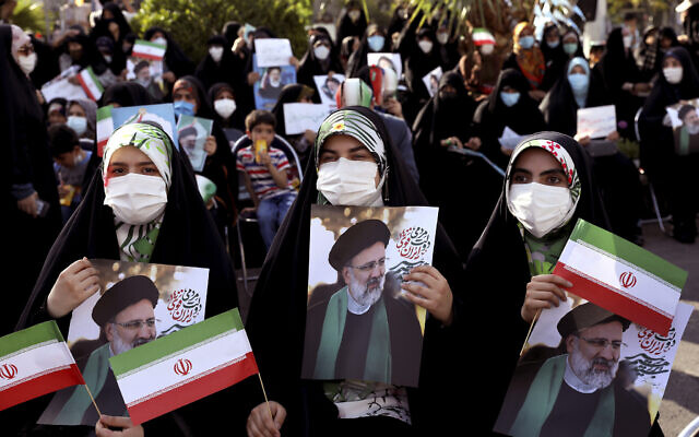 Supporters of presidential candidate Ebrahim Raisi hold signs during a rally in Tehran, Iran, June 16, 2021. (AP Photo/Ebrahim Noroozi)