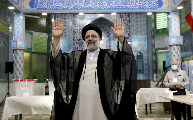 Ebrahim Raisi, who went on to win Iran's presidential election, waves after casting his vote at a polling station in Tehran, Iran, on June 18, 2021. (Ebrahim Noroozi/AP)