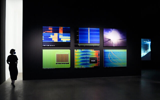 A woman walks through an exhibition by American artist and filmmaker Laura Poitras, near the art work 'Anarchist' by Laura Poitras in collaboration with Henrik Moltke, at the NKB gallery in Berlin, Germany, on June 18, 2021. (AP Photo/Markus Schreiber)