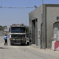 A Hamas security officer checks a truck entering Gaza at the gate of the Kerem Shalom cargo crossing with Israel, in Rafah, southern Gaza Strip, June 21, 2021. (Adel Hana/AP)