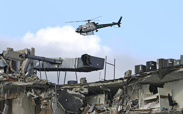 A Miami-Dade Police helicopter flies over the Champlain Towers South Condo after the multistory building partially collapsed, June 24, 2021, in Surfside, Florida. (David Santiago/Miami Herald via AP)