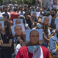 Angry demonstrators carry pictures of Nizar Banat, an outspoken critic of the Palestinian Authority, and chant anti-PA slogans during a rally protesting his death, in the West Bank city of Ramallah, on June 24, 2021. (AP Photo/Nasser Nasser)
