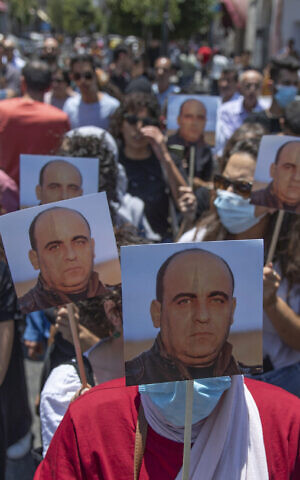 Angry demonstrators carry pictures of Nizar Banat, an outspoken critic of the Palestinian Authority, and chant anti-PA slogans during a rally protesting his death, in the West Bank city of Ramallah, June 24, 2021. (AP Photo/Nasser Nasser)