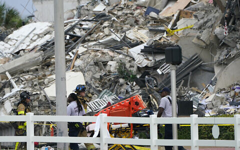 Miami-Dade Fire Rescue personnel walk with an empty stretcher past the scene where a wing of a 12-story beachfront condo building collapsed, Thursday, June 24, 2021, in the Surfside area of Miami. (AP Photo/Lynne Sladky)